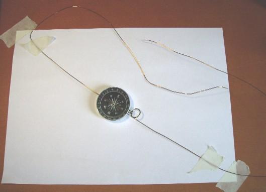 f3d93522ac4 3. Estender sobre a bússola um fio de cobre na direção indicada pela agulha  (que será a Norte-Sul da Terra) e fixá-lo à mesa com o auxílio de fita  adesiva.